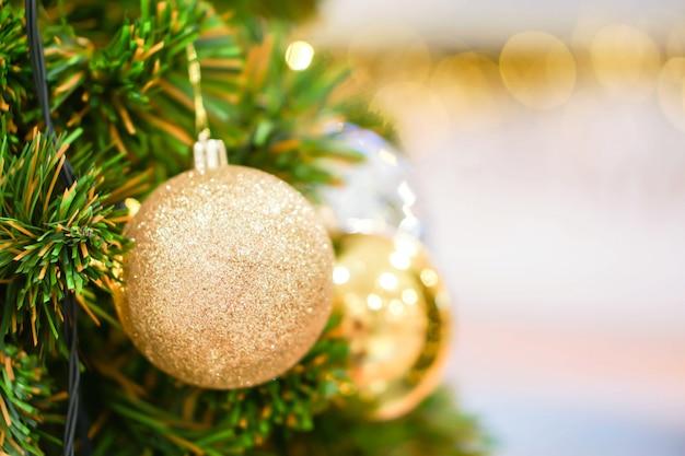 Goldene weihnachtsbälle verziert auf kiefer am weihnachtstag mit undeutlichem hintergrund und bokeh der weihnachtsbeleuchtung.