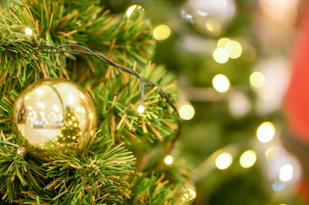 Goldene weihnachtsbälle verziert auf kiefer am weihnachtstag mit undeutlichem hintergrund