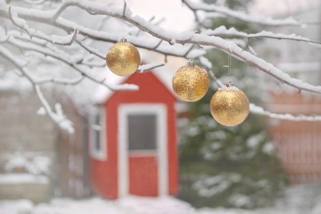 Goldene weihnachtsbaumkugeln auf ästen und winterschnee. weihnachtsbälle in der nähe von pelzbäumen, die mit einem schnee und einem kleinen roten holzhaus bedeckt sind.