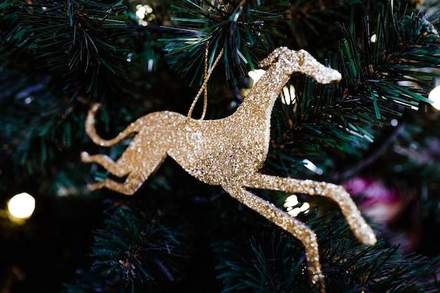 Goldene weihnachtsdekoration am baum spielzeug in form eines hundes festliche magische weihnachten