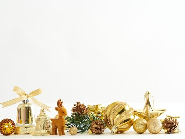 Goldene weihnachtsdekoration mit rentier, kugeln, sternen und tannenzweig auf weißem hintergrund