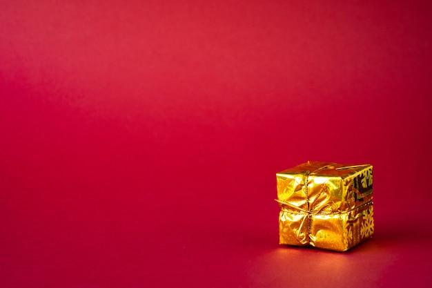 Goldene weihnachtsgeschenkbox auf rot