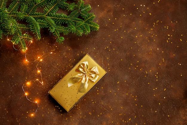 Goldene weihnachtsgeschenkbox mit goldener schleife auf braunem hintergrund, fichtenzweig mit und einer girlande und goldsternkonfetti. festliche stimmung. flache lage. draufsicht. speicherplatz kopieren.