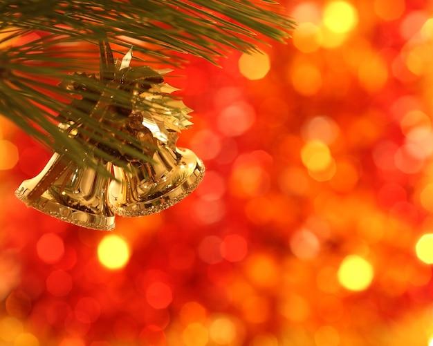 Goldene weihnachtsglocken auf tannenzweig
