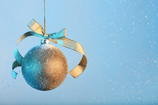 Goldene weihnachtskugel auf blauem schnee