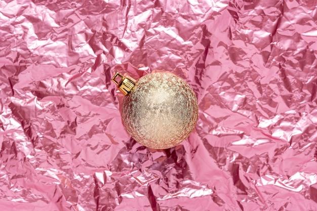 Goldene weihnachtskugel auf rosa zerknittertem folienhintergrund.
