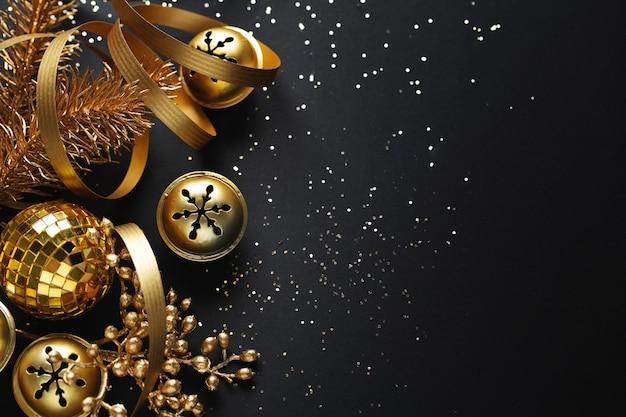 Goldene weihnachtskugeln auf dunkelheit. flache lage.