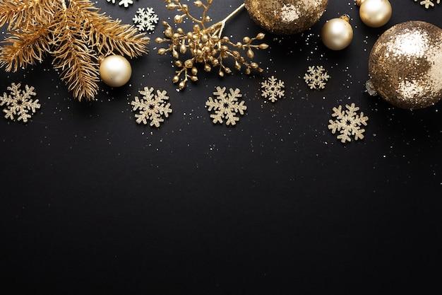 Goldene weihnachtskugeln auf dunklem hintergrund. flache lage.
