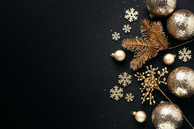 Goldene weihnachtskugeln auf schwarz. flache lage.