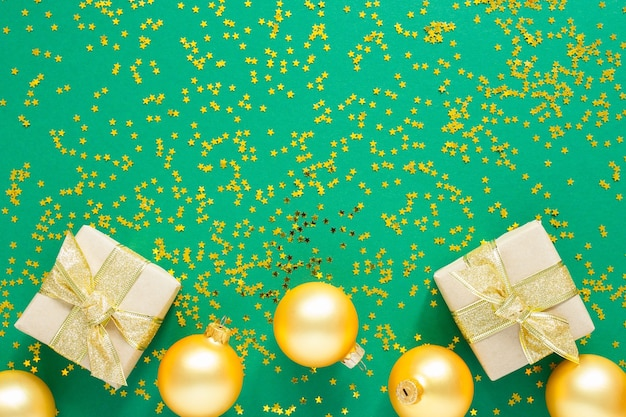 Goldene weihnachtskugeln und geschenkboxen auf grüner oberfläche mit goldenen glitzersternen, flache lage, draufsicht