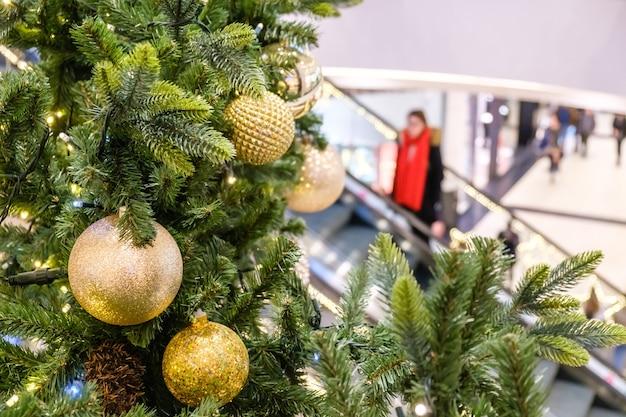 Goldene weihnachtskugeln und girlande auf geschmücktem tannenbaum in der shop mall verschwommene menschen auf rolltreppe