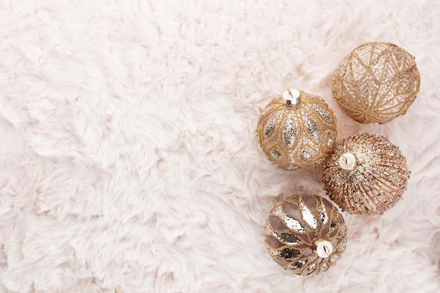 Goldene weihnachtskuschelbälle mit wollhintergrund.