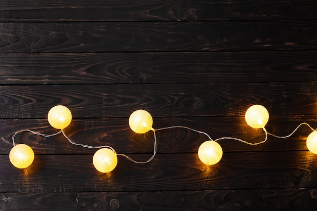 Goldene weihnachtslichter auf dunklem holz