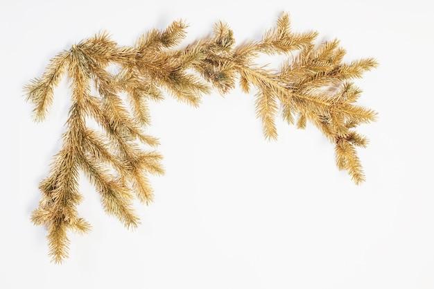 Goldene weihnachtstannenzweige auf weißem hintergrund