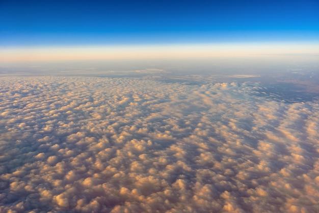 Goldene wolke über dem blauen himmel außenseite über ansicht von den flugzeugseitenfenstern, wenn sonnenaufgang
