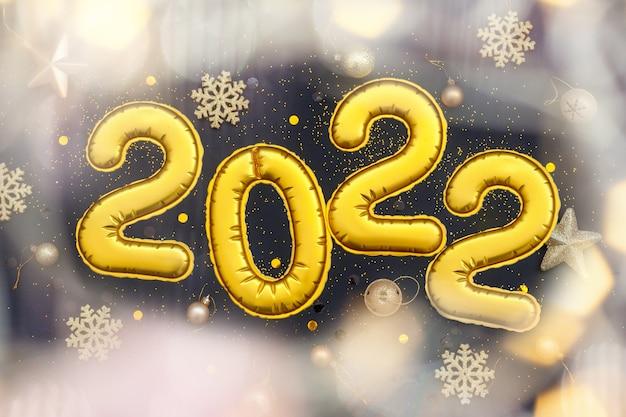 Goldene ziffern 2022-zahlen des guten rutsch ins neue jahr liegen auf schwarzem hintergrund. flache lage, weihnachtsfeierdekoration oder postkartenkonzept.