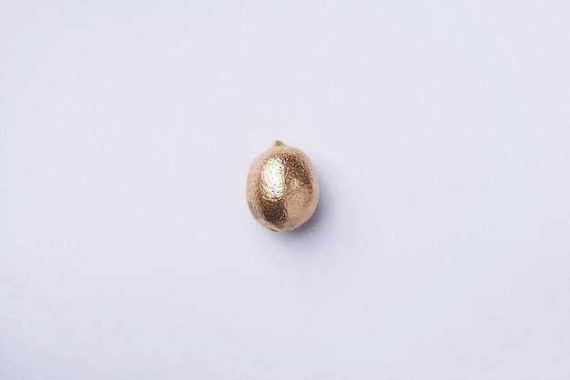 Goldene zitrone. kreatives lebensmittelkonzept. ansicht von oben. flach liegen. einzelne exotische goldfrucht.