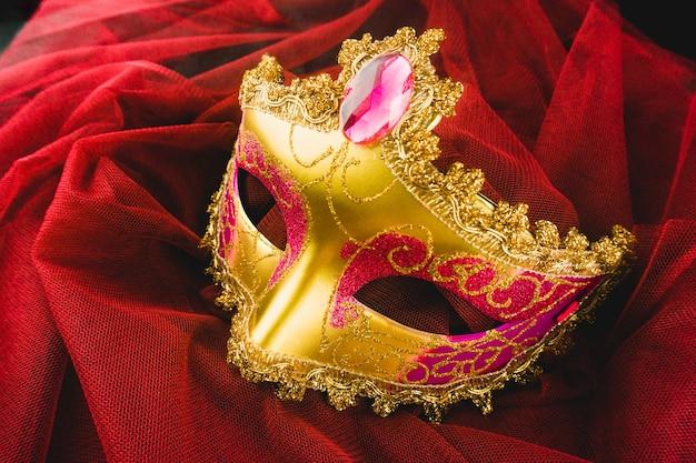 Goldenen venezianischen maske auf einem roten stoff