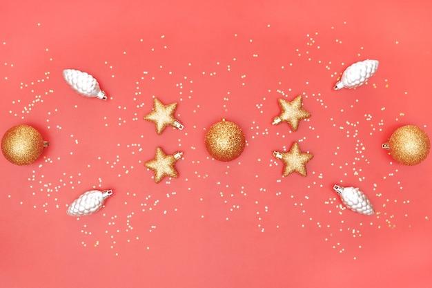 Goldener ball, stern und glocke auf rosa lebendem korallenrotem hintergrund für geburtstag