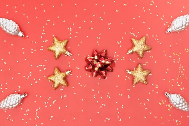 Goldener ball, stern und glocke auf rosa lebendem korallenrotem hintergrund für geburtstagszeremonie