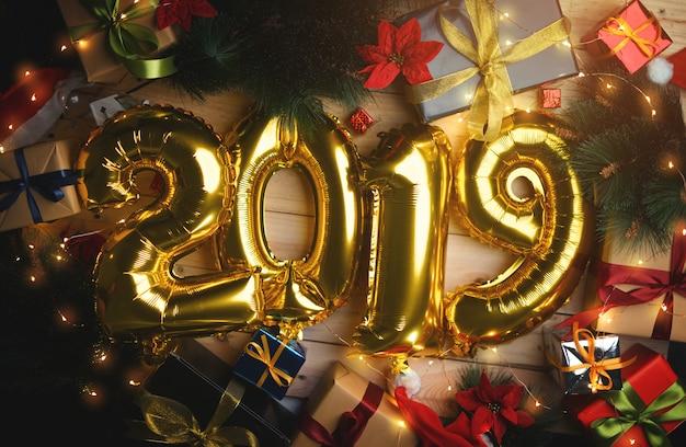 Goldener ballon 2019 zwischen weihnachtsdekoration. draufsicht