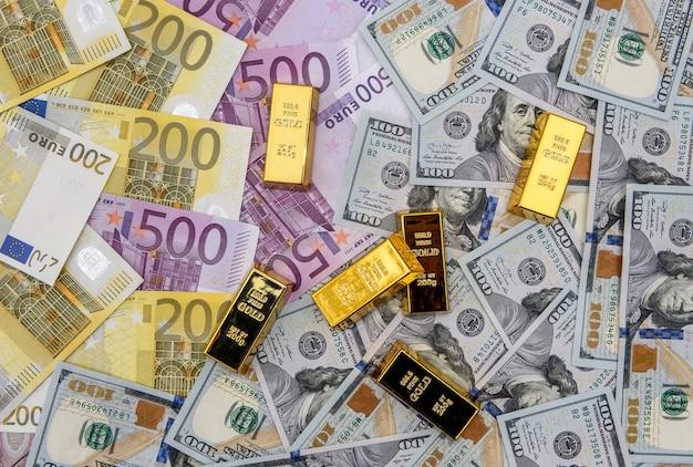 Goldener barren auf us-dollar und euro-banknoten