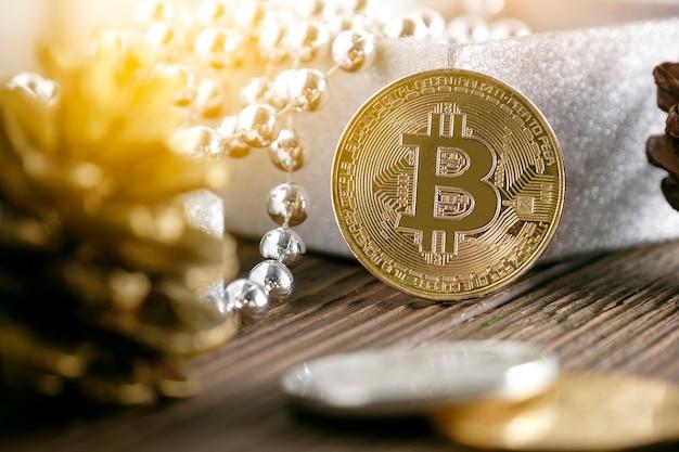 Goldener bitcoin gesetzt nahe geschenkbox und kiefernkegel