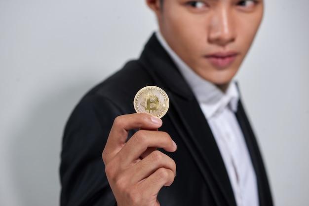 Goldener bitcoin in der hand eines mannes, digitales symbol einer neuen virtuellen währung