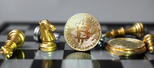 Goldener bitcoin-kryptowährungs-münzstapel und schachfigur auf schachbrett.