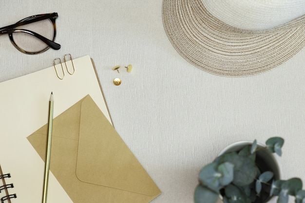Goldener bleistift, büroklammern, stifte, handwerksumschlag auf geöffnetem anmerkungsbuch mit hut