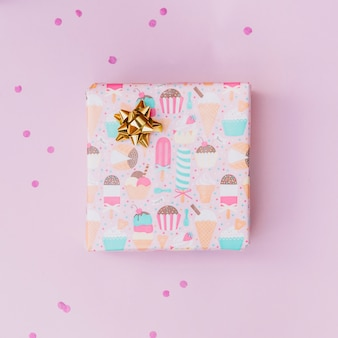 Goldener bogen auf eingewickelter geschenkbox über dem rosa hintergrund