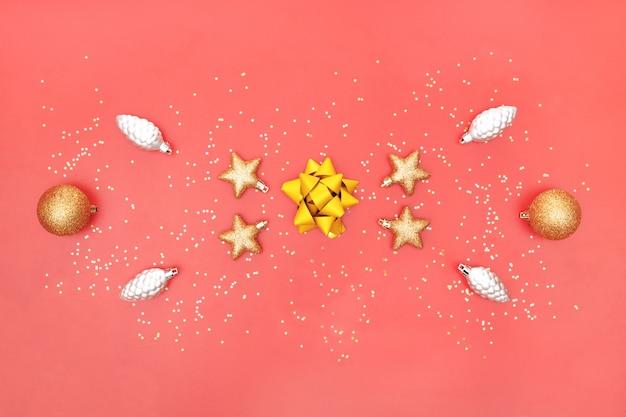 Goldener bogen, stern, glocke und ball auf rosa lebendem korallenrotem hintergrund für geburtstag