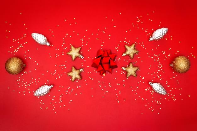 Goldener bogen, stern, glocke und ball auf rotem hintergrund für geburtstag, weihnachten