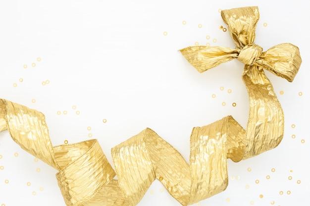Goldener bogen und goldenes konfetti auf weiß