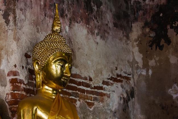 Goldener buddha neben alten wänden in den thailändischen tempeln
