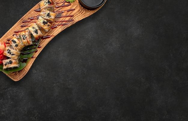 Goldener drache der sushirolle auf holzbrett horizontal auf schwarz mit platz für text