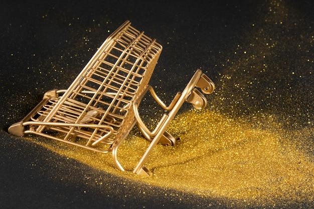 Goldener einkaufswagen auf schwarzem hintergrund