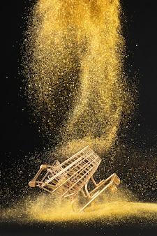 Goldener einkaufswagen im goldenen glitzer