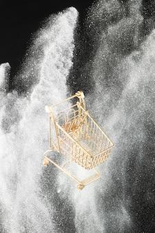 Goldener einkaufswagen im weißen glitzer