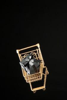 Goldener einkaufswagen mit schwarzem geschenk