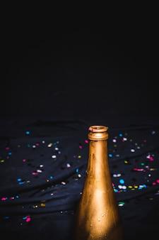 Goldener flaschenhals mit konfetti