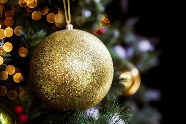 Goldener glänzender glitzernder ball am weihnachtsbaum mit verschwommenen lichtern. urlaubskonzept. nahaufnahme.