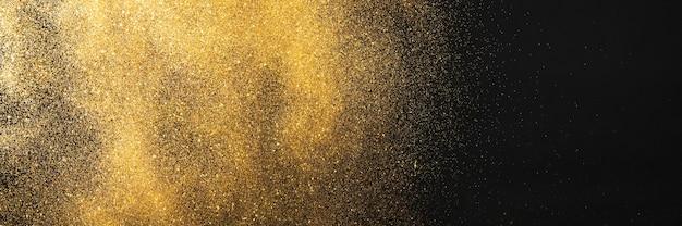 Goldener glitzer auf schwarzem hintergrund