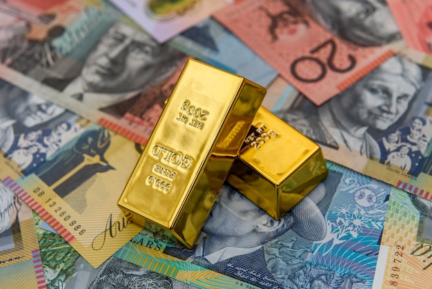Goldener goldbarren bei australischen dollar-banknoten schließen