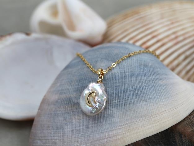Goldener halbmond barockperlenanhänger mit goldkette auf meeresmuschelhintergrund