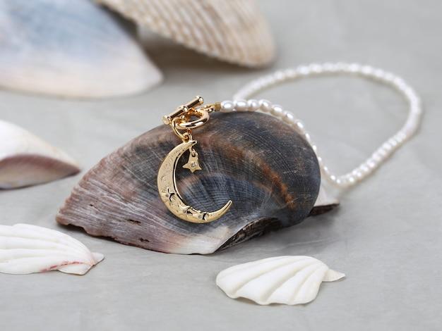 Goldener halbmondanhänger mit perlenkette auf meeresmuschelhintergrund