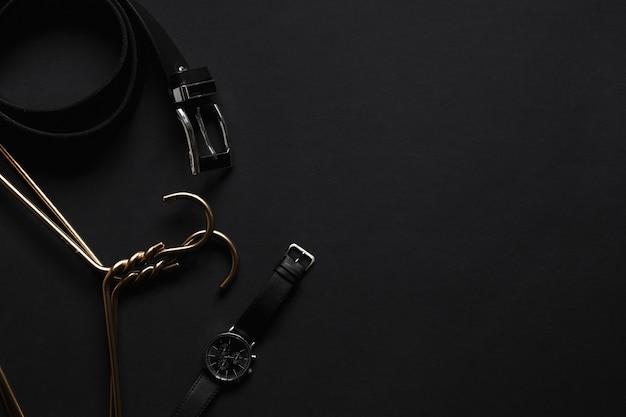 Goldener kleiderbügel, schwarzer gürtel und armbanduhr auf schwarzem tisch. herrenaccessoires und beauty-equipment.