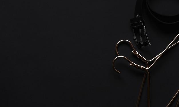 Goldener kleiderbügel und schwarzer gürtel auf schwarzem tisch. herrenaccessoires und beauty-equipment.