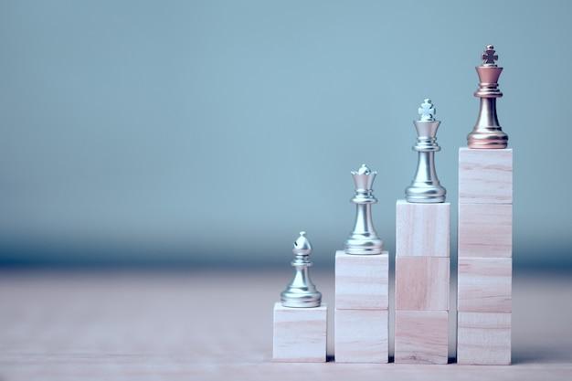 Goldener könig schach an siegerposition auf holzwürfel des schachspiels