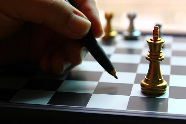 Goldener könig schach auf schachbrett mit unschärfe-handgriff-stift, der auf schachbrett zeigt